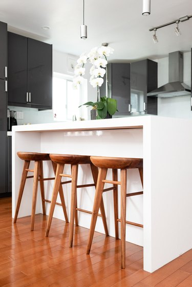 White kitchen island with wood stools and an orchid plant
