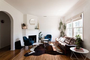 Living room with blue tufted accent chairs, leather sofa, white mantel fireplace, animal skin rug, and round accents.