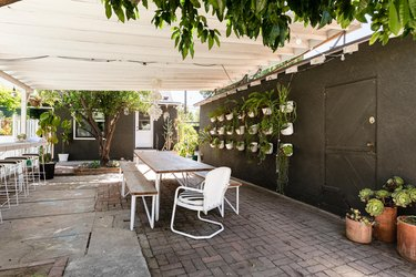 Wood pergola over wood and white metal dining furniture on a concrete brick patio, and a black wall with hanging plants.