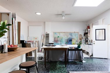 Garage Ideas in Artist gallery with white walls, with large painting attached to one wall, next to shelves with painting supplies and small kitchen island with brown stools