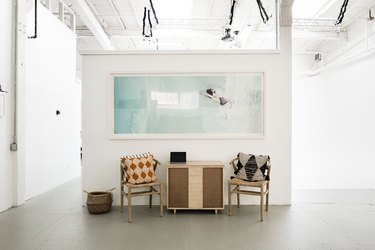 White-walled art gallery with large print, pillowed chairs, and wood cabinet on concrete floor