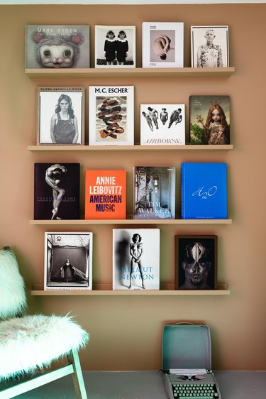 Homeschool Organization with Shelving units with magazines against brown wall with turquoise chair
