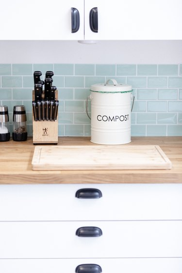 Kitchen counter with knife set, salt and pepper shakers, and compost bucket on wood countertop and white shelves against tiled backsplash