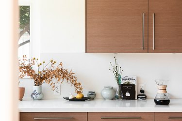 Wood kitchen cabinets, and a white counter with vases of flowers, pottery pieces, and a Chemex coffee.
