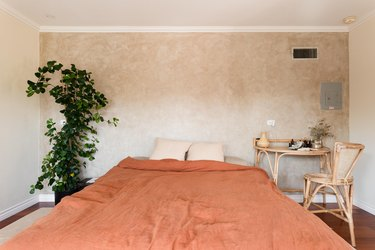 Bedroom with a texture beige accent wall, orange bedding, Boho rattan desk and chair set, and a plant on a trellis.
