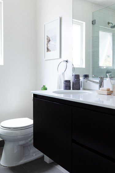 white toilet and dark wood vanity with white bathroom countertop and chrome hardware
