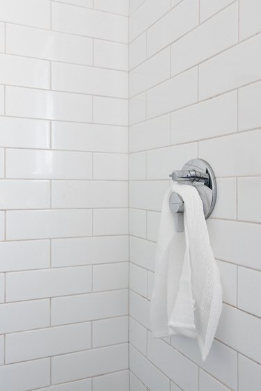 white subway tile with chrome shower handle with white towel