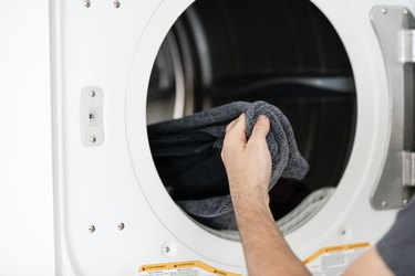 modern white dryer with hand reaching for laundry