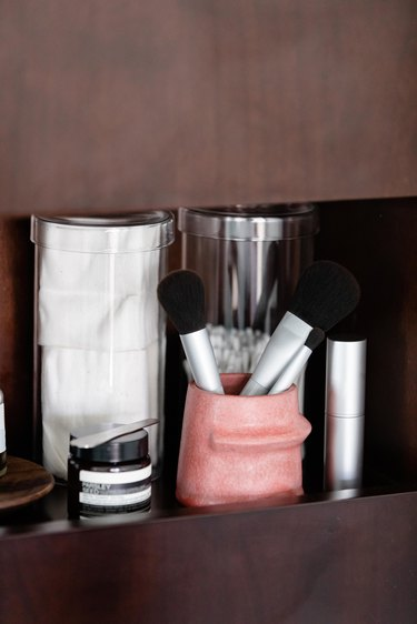 Makeup Organizer Ideas for skincare and makeup brushes on wood shelving