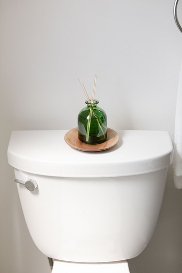 glass diffuser on top of white toilet