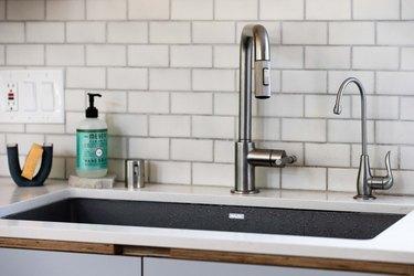 undermount kitchen sink with white countertop and subway tile backsplash