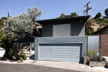 Blue panel-style garage door with matching blue exterior