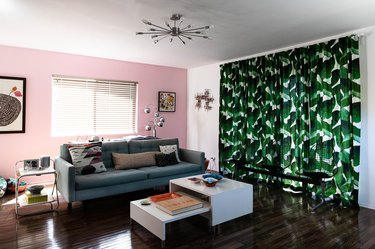 room with pink wall and green botanical curtain with couch and coffee table nearby