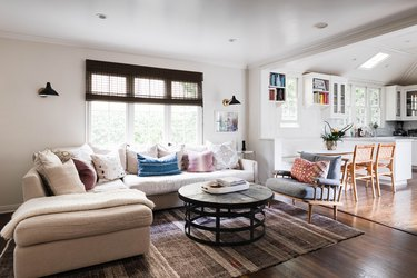 A living room with a roller shade on the window