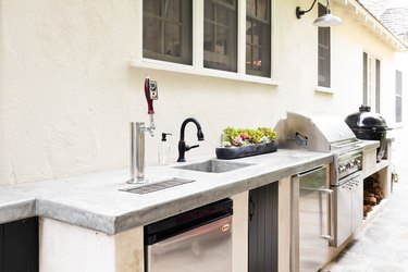 outdoor kitchen with stainless steel appliances and stone countertop
