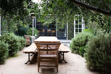 wooden outdoor dining table with benches and rattan chairs outside ivy covered home