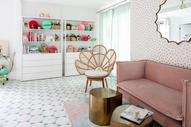 pink room ideas with Pink couch in room with white walls, tiled floors and wallpaper, oval mirror, cane side chair and hold coffee tables.