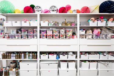Craft Storage Shelves with craft supplies in white and clear containers.