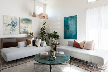 color scheme in modern-contemporary living room with couches, pillows, paintings, plant, and marble-top coffee table against white walls