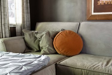 grey microfiber couch with orange round pillow