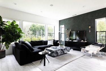 Black Room Ideas with A modern living room with green walls, black sofas and gray wood floors