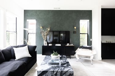 Modern living room with green walls and black-white furnishings