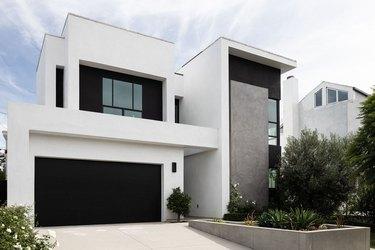 Black and white minimalist-modern house with black garage door