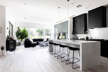 A modern kitchen with gray wood floors, black cabinets and white kitchen island