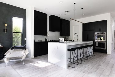Modern kitchen with black cabinets, gray wood floors and white counters
