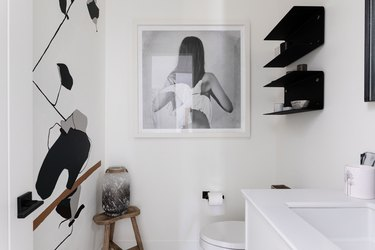 White walled bathroom with black shelving, wall decals and photograph art