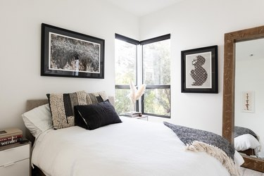 White-walled bedroom with a corner window and gray-black accents