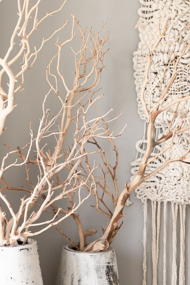 Dried beige sea plants in white vases and a textile wall hanging