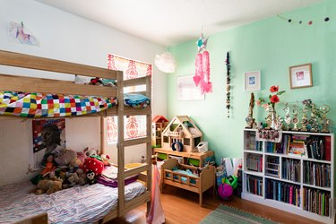 A kid's room with white-green walls, a wood bunk bed, toys, and bookcase