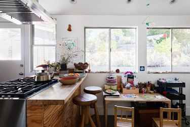A kitchen with wood countertops, stove vent, stools and a kid's art desk