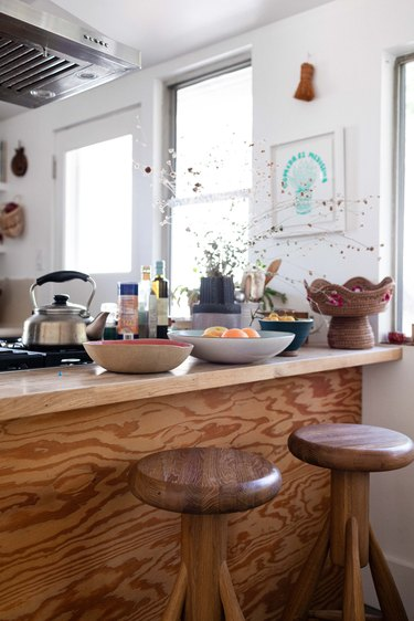 A wood countertop with wood stools in a white-walled kitchen