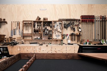 A woodworking studio with tools, wood walls and storage