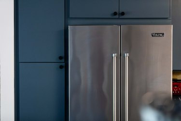 stainless steel refrigerator built into blue kitchen cabinets