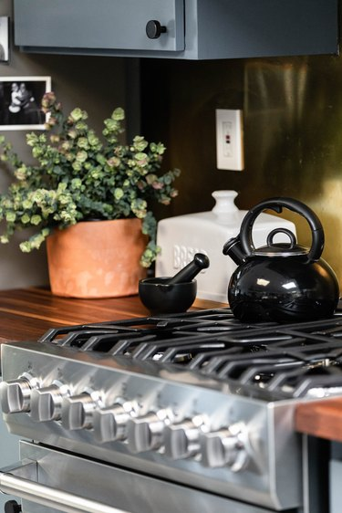 Gas stove with black kettle, white bread box and plant on countetrop