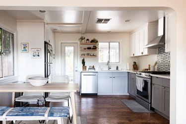 A minimalist kitchen with white walls, gray cabinets and dark wood floor