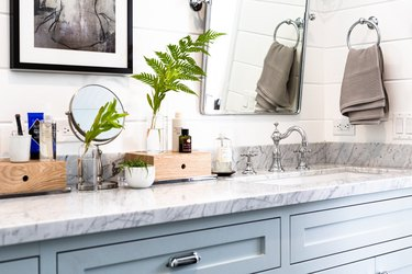 blue bathroom vanity, marble countertop, undermount sink with silver faucet and handles, various bathroom products in wood boxes on top of the counter, a rectangular mirror over the sink, a gray hand towel hanging in a mounted towel ring