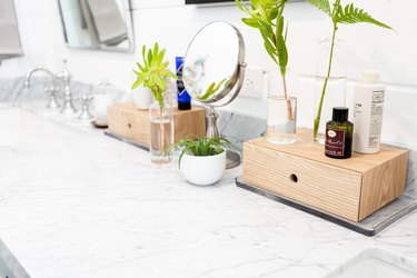 Makeup Organizer Ideas on Bathroom vanity, wood storage container drawers, cosmetics, mirror, plants, sink, mirror.