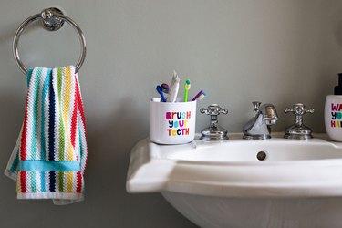 bathroom sink with rainbow colored hand towel in kid's bathroom