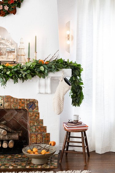 neutral Christmas decorations list with garland and candlesticks on mantel