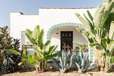 a Spanish style home with green plants in the front yard