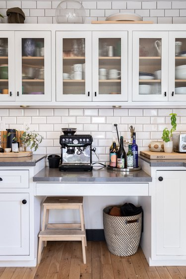 Kitchen with white cabinets, subway tile, coffee maker, stool.