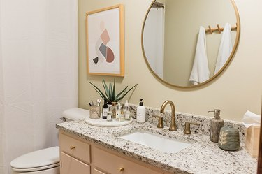 Beige painted wood vanity cabinet with a granite or quartz counter, in a neutral bathroom
