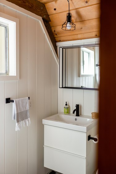 White-walled bathroom with wood ceiling with mirror, small white sink, black faucet, and white hand towel