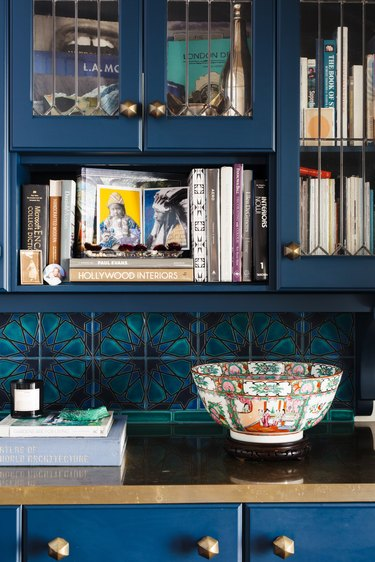 Dark blue kitchen cabinet with gold counter and knobs. Turquoise geometric floral backsplash, vintage bowl and books.