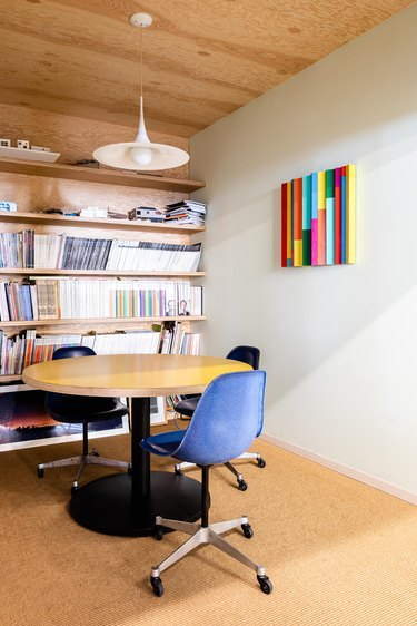 An office with white walls and wood shelving