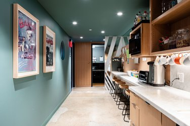An office kitchen with green walls and wood cabinets